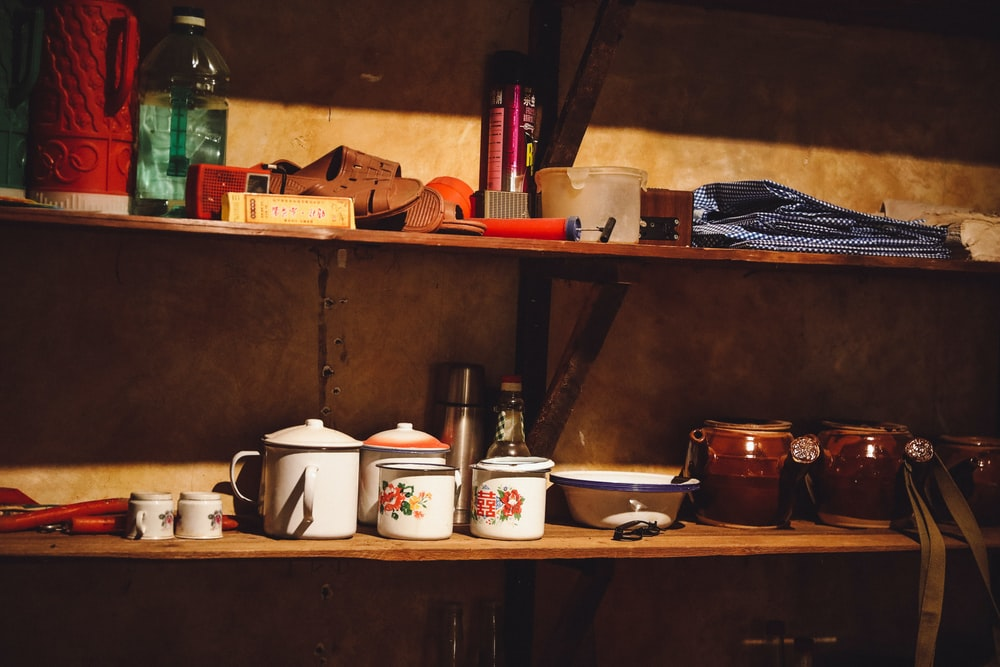 white ceramic cup on brown wooden shelf