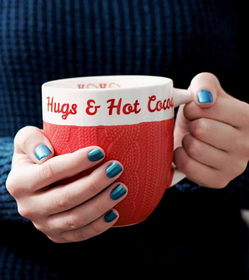 person holding white and red ceramic mug