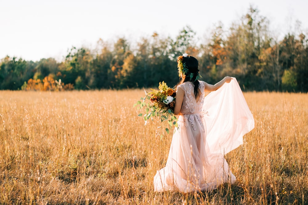 woman wearing white floral dress walking on brown grass field