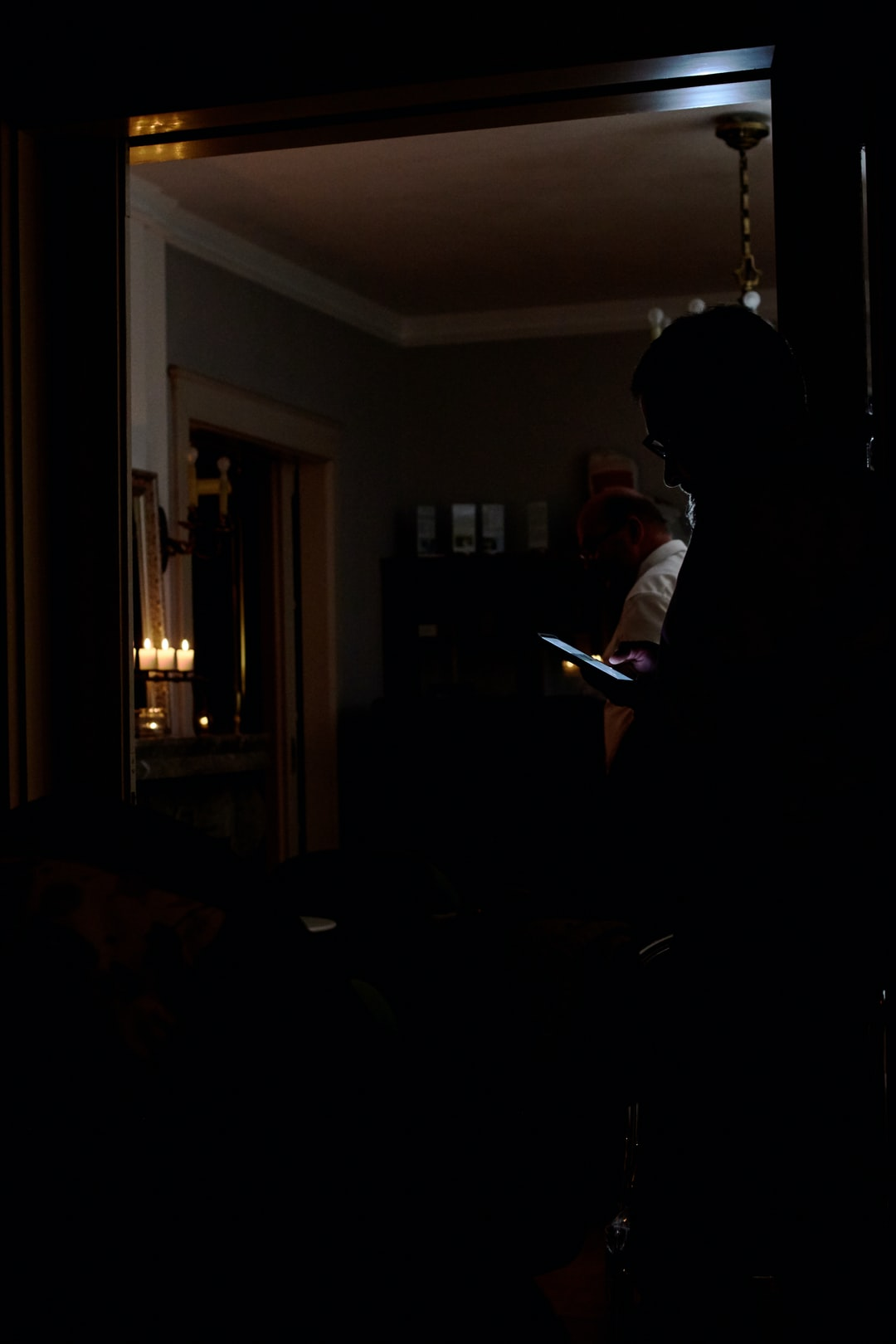 man checking his smartphone in a moody lit room.