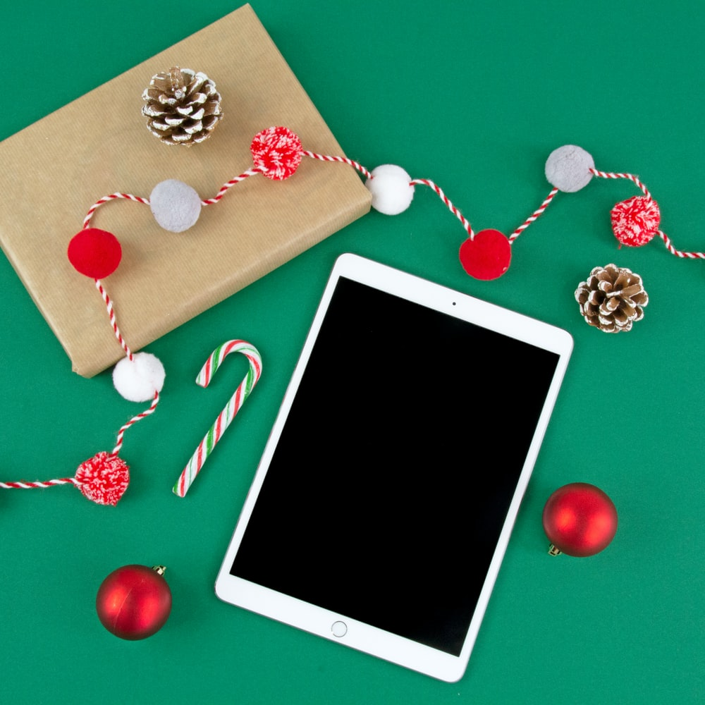 turned-off iPad by box, pinecones and baubles