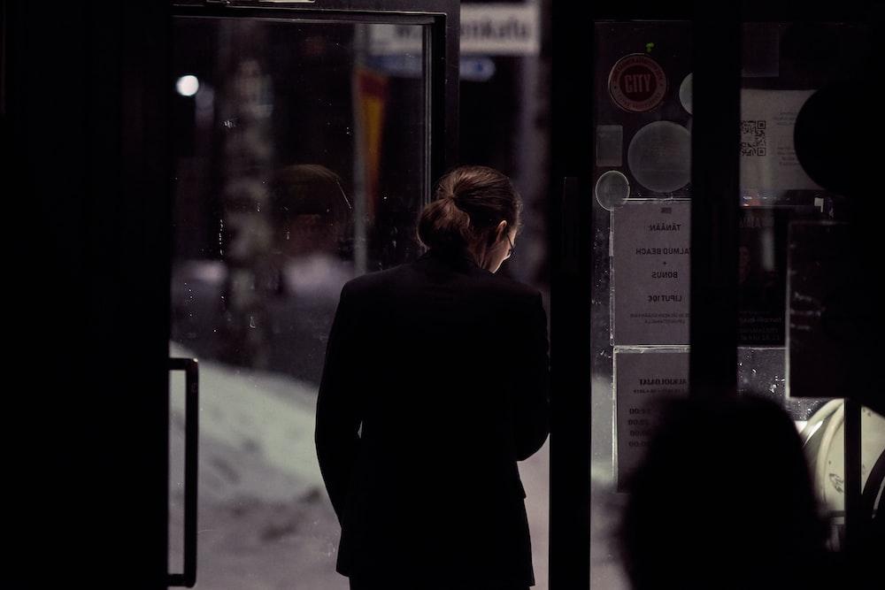 person in black top standing beside door