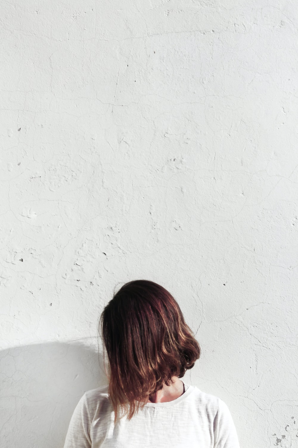 woman in white shirt leaning on wall during daytime