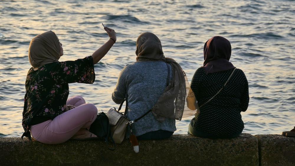 three women sitting beside body of water
