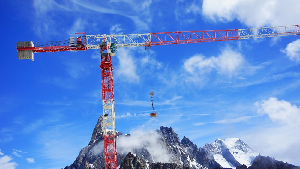 white and red crane lift near mountain under blue skies during daytime