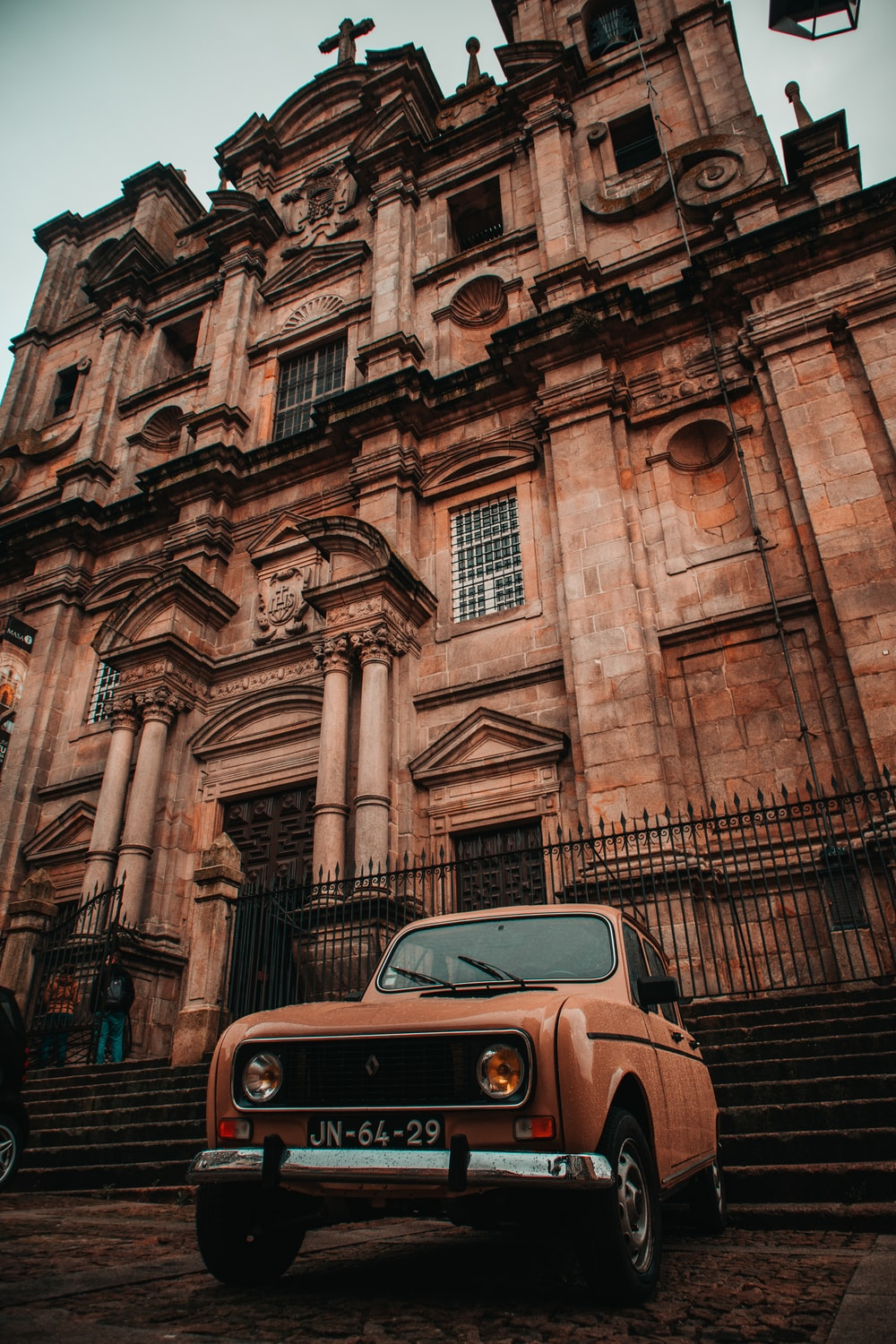 brown vehicle parked beside building