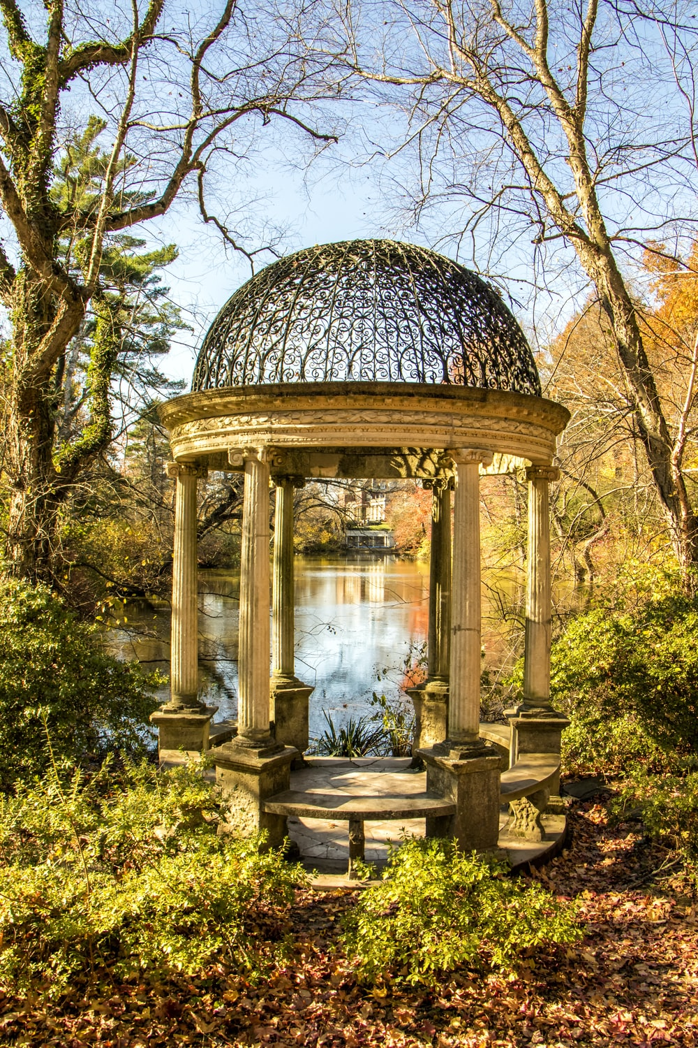 brown concrete gazebo near lake