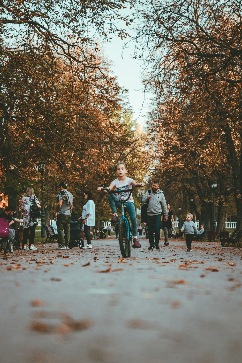 girl riding bicycle on pathway surrounded by people