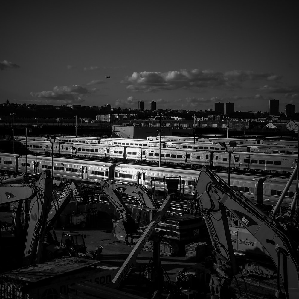 grayscale photography of city with high-rise buildings viewing train station