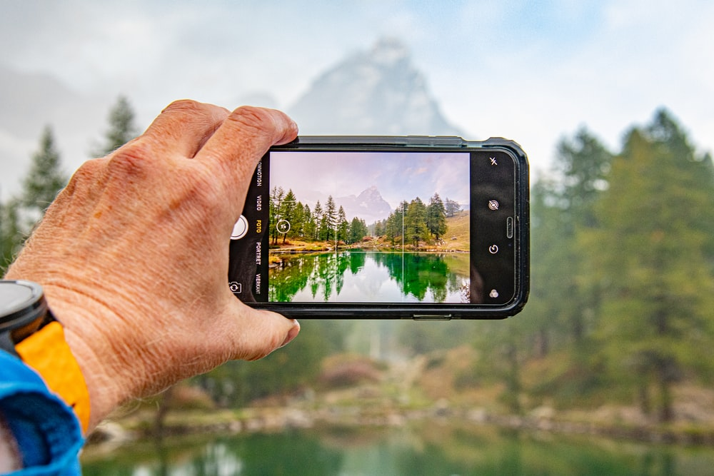 man taking picture of lake and trees