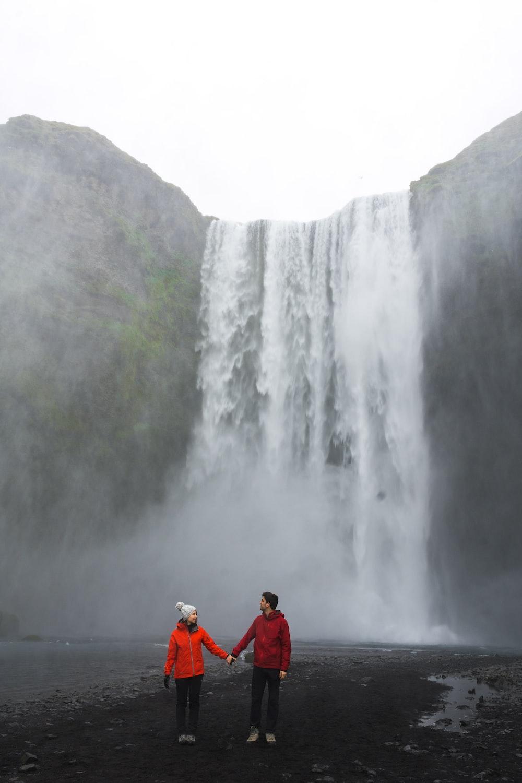 couple standing near waterfalls