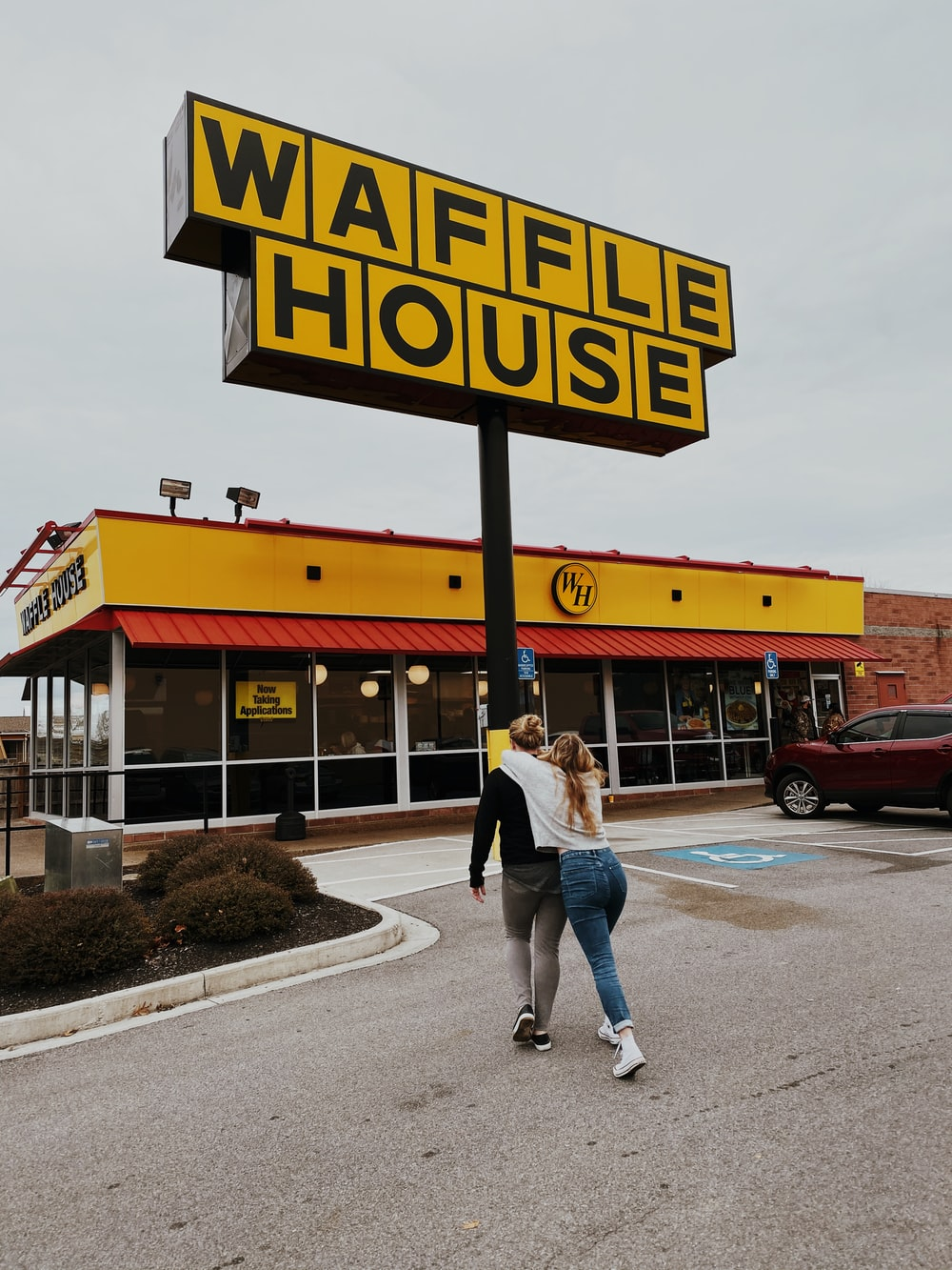 man and woman walking towards Waffle House store