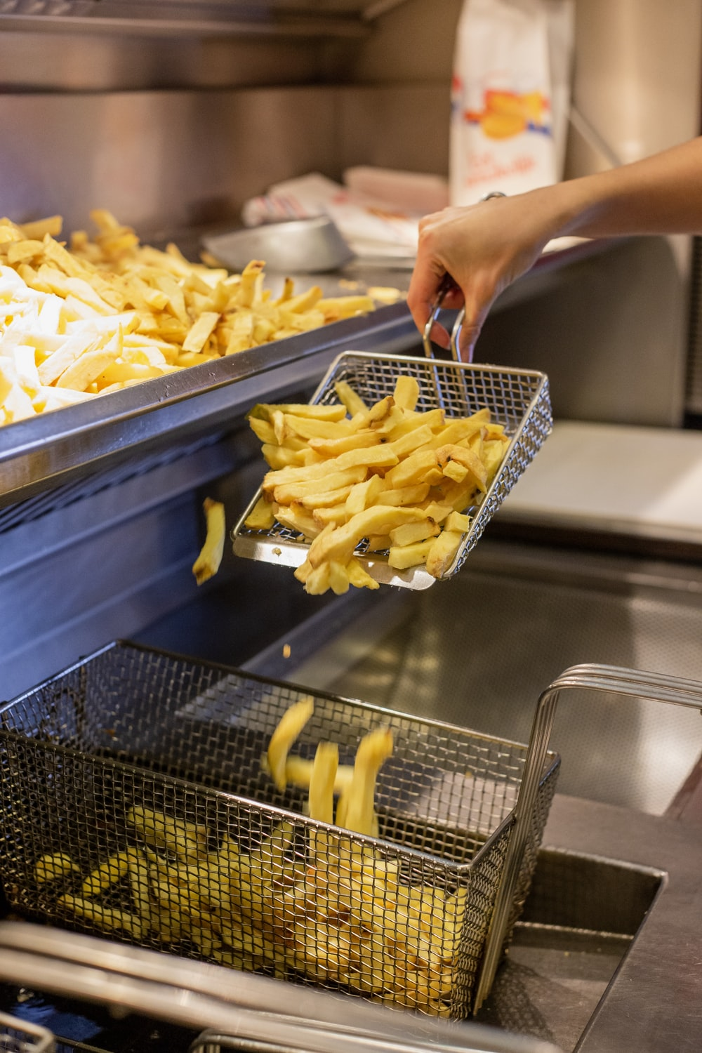 person holding deep frying basket of fries