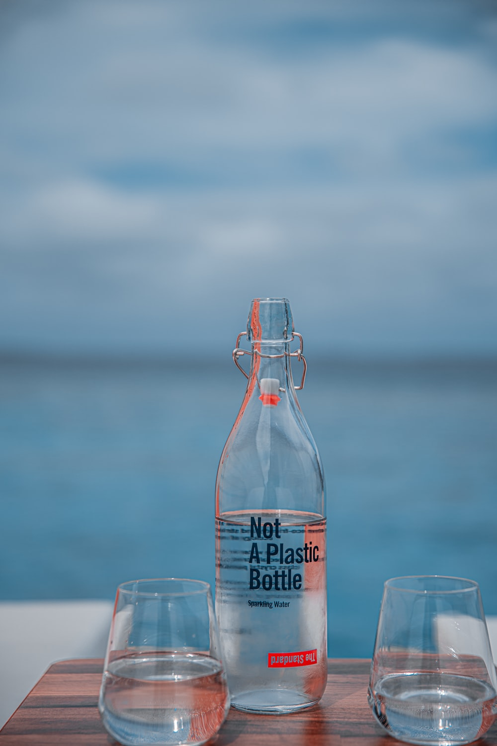 selective focus photography of plastic bottle between rock glasses during daytime