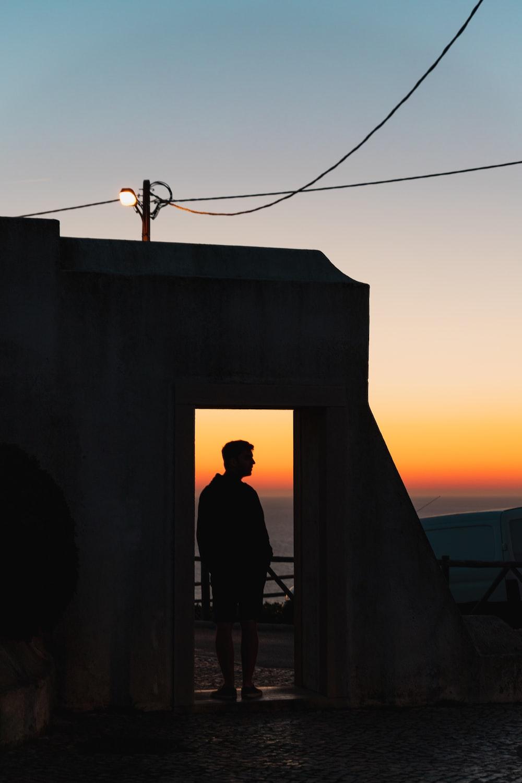 silhouette of person standing near open door