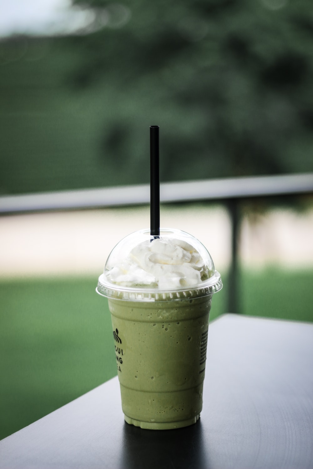 green disposable cup on black surface