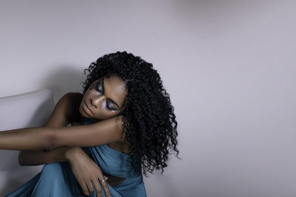 woman in blue top sitting beside wall