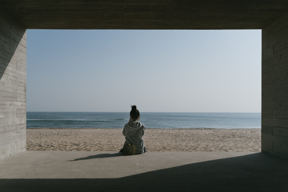 photography of person facing on seashore during daytime