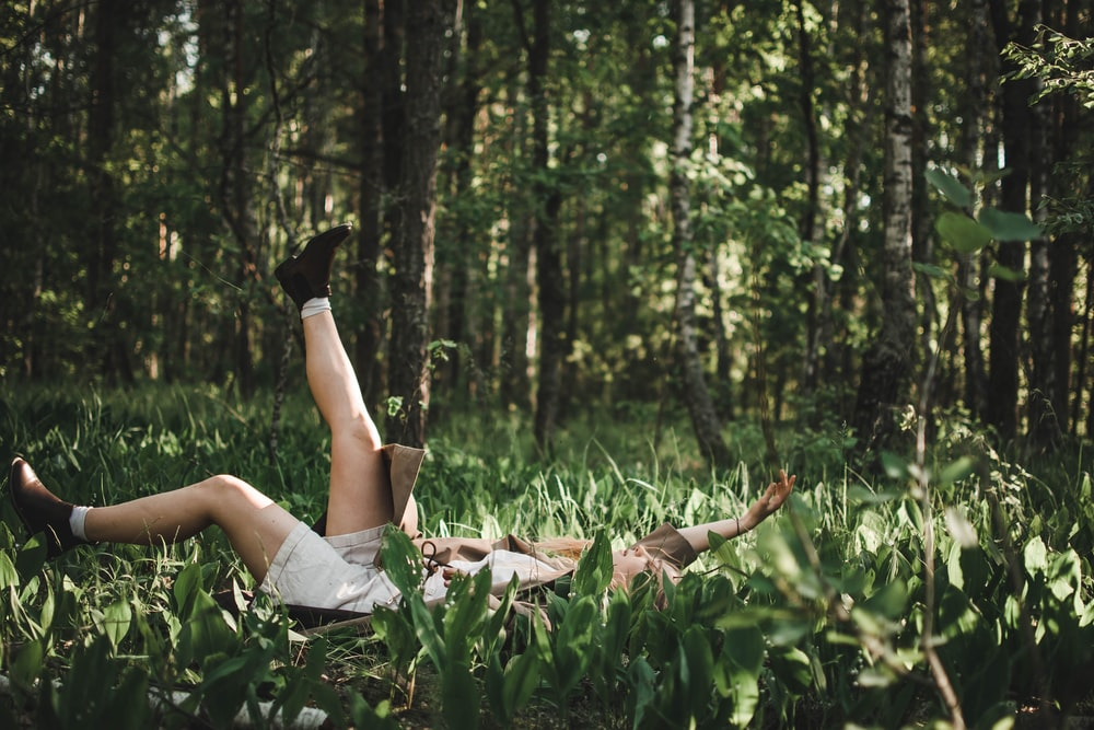 person lying on green grass field during daytime