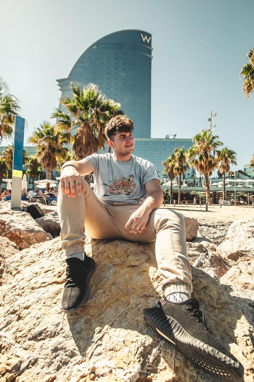 man wearing grey t-shirt wearing brown pants sitting on rocks