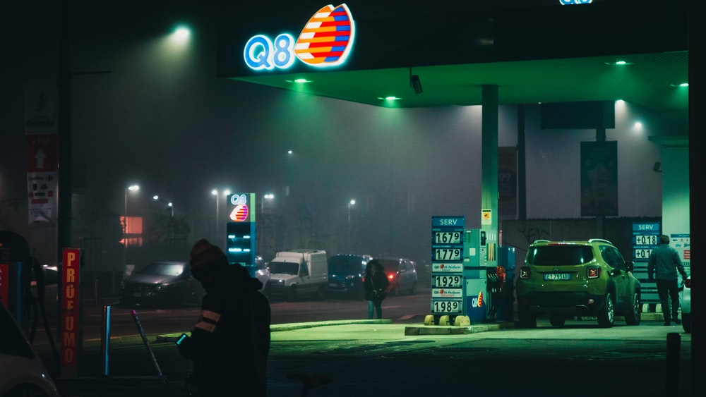 car and people at the Q8 gas station during night