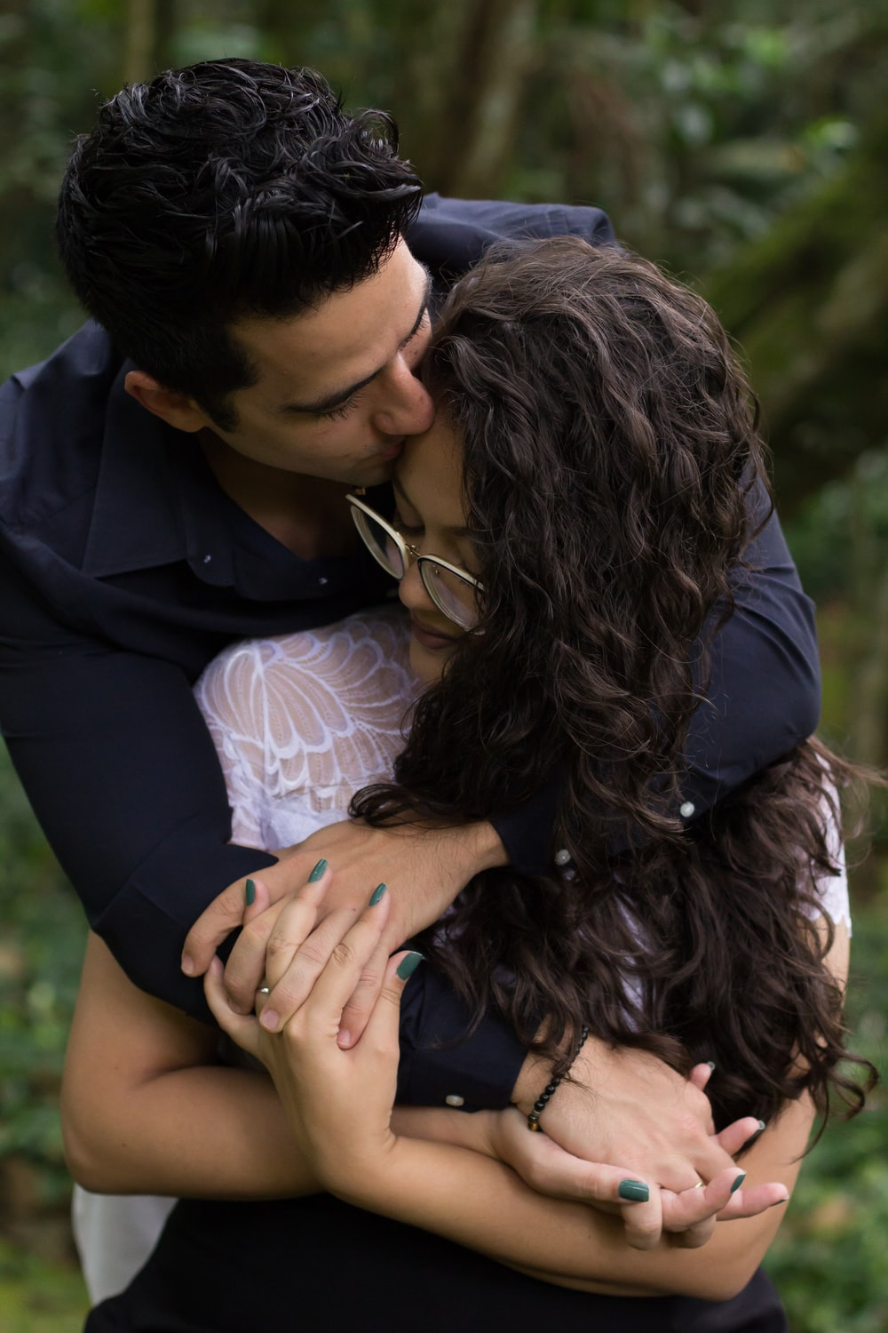 man hugging woman on her back and kissing her forehead