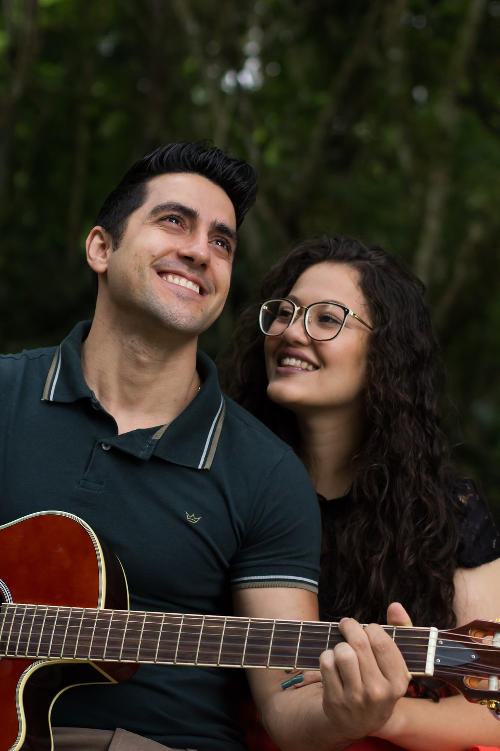 selective focus photography of smiling woman beside man who play guitar during daytime