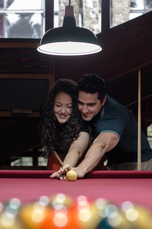 man teaching a woman how to play pool