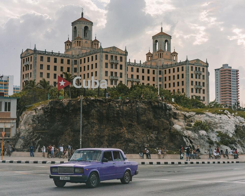 purple sedan on road near building during day