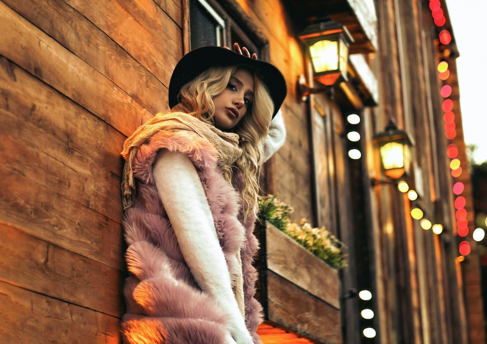 woman in pink fur vest leaning on wall