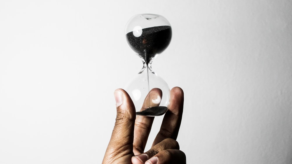 person holding hourglass