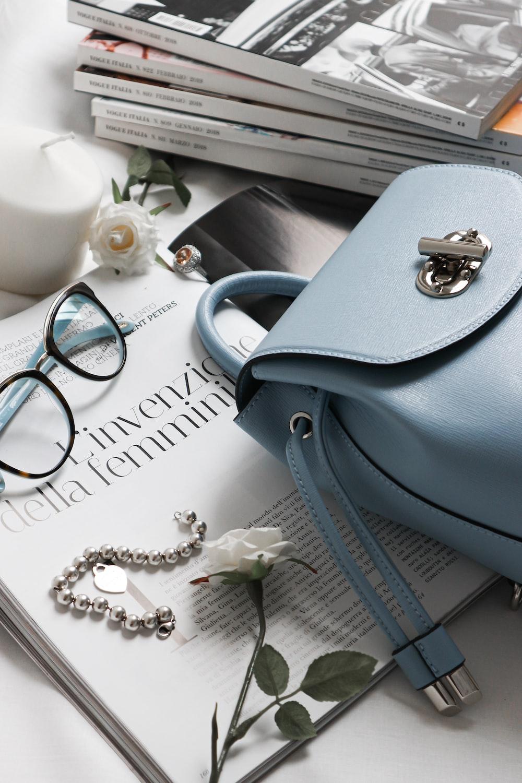 gray leather handbag beside eyeglasses and books