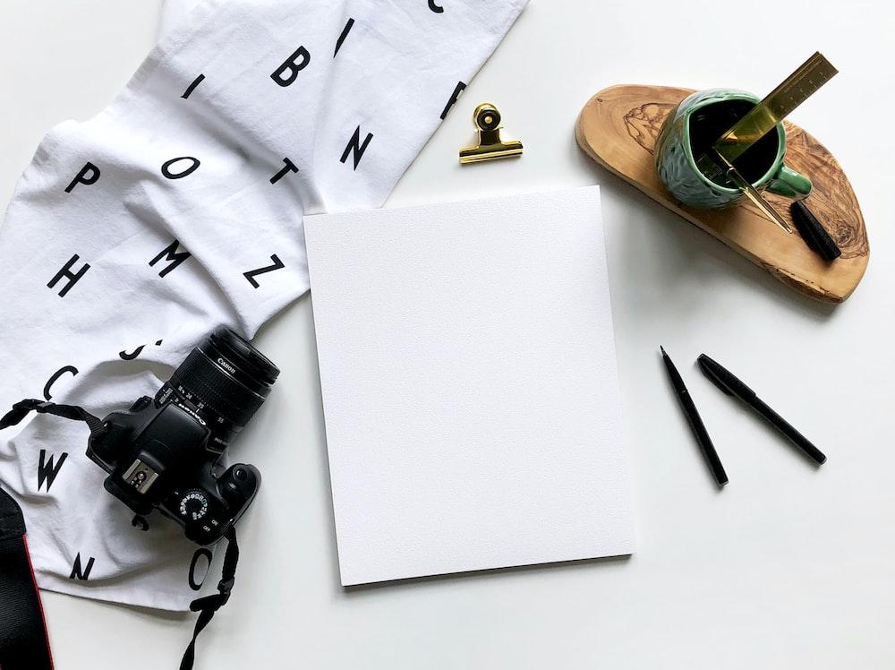 black DSLR camera beside white printer paper