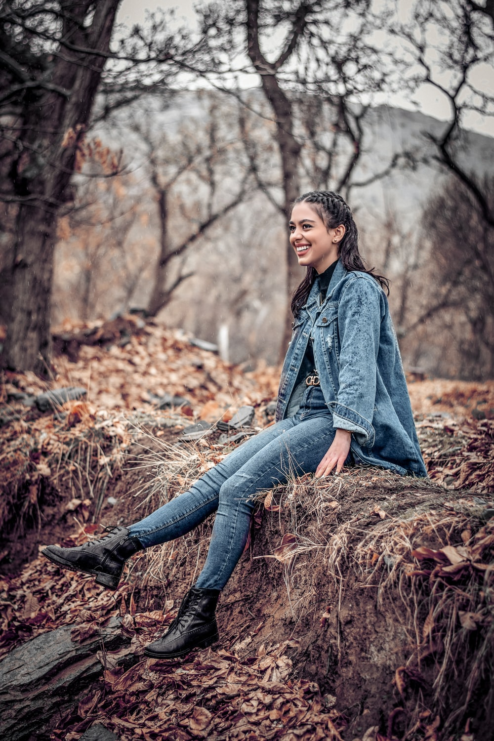 woman smiling and sitting on soil ground near trees