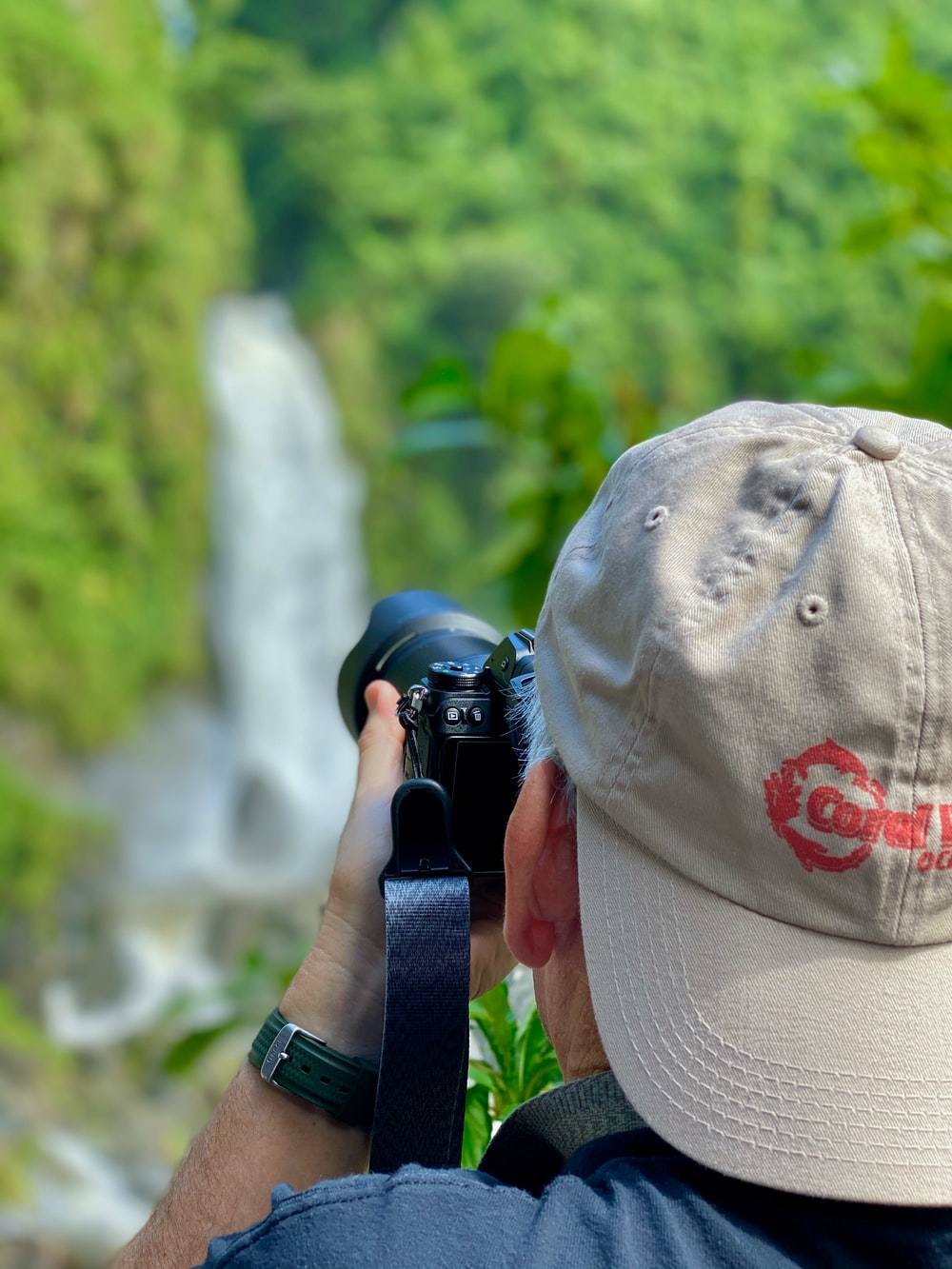 person taking photo of waterfall during daytime