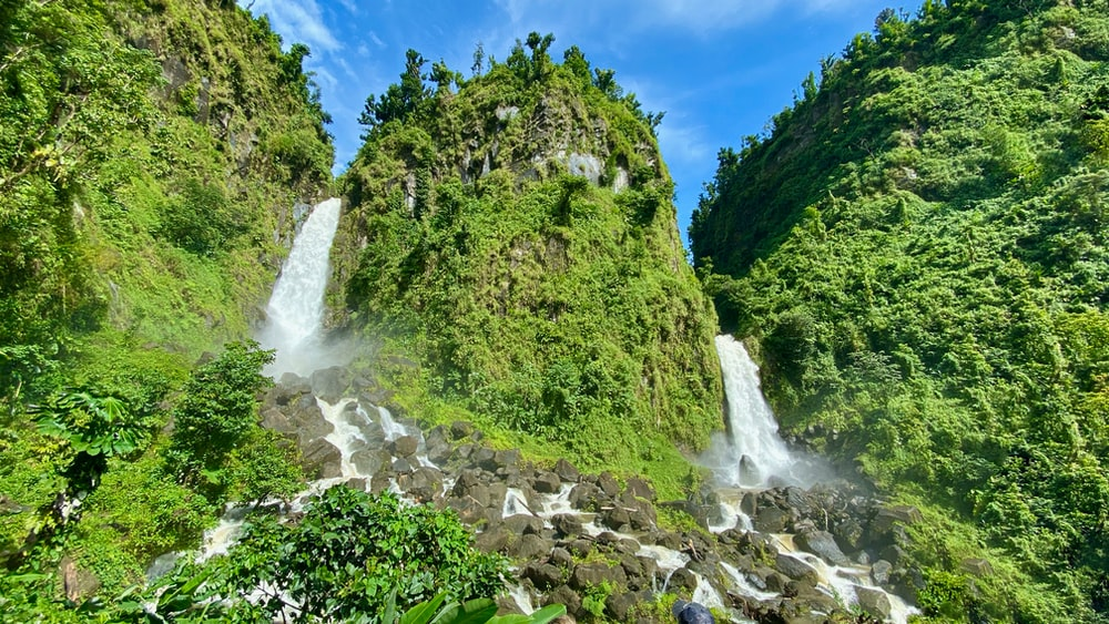 waterfalls and grass mountain during day