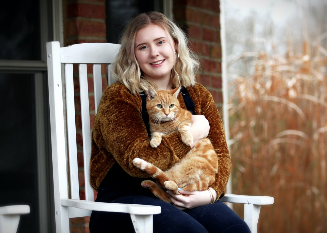 A girl holds a striped cat on her front porch in front of a wheat field in the fall.