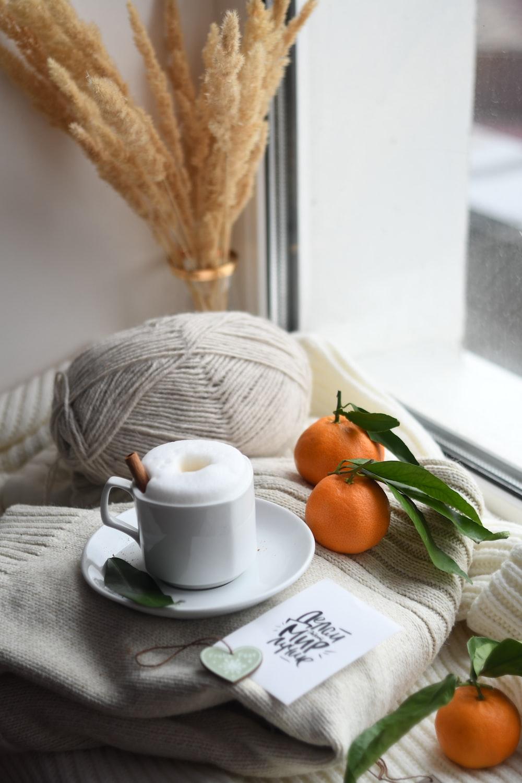 mug and citrus fruits on window