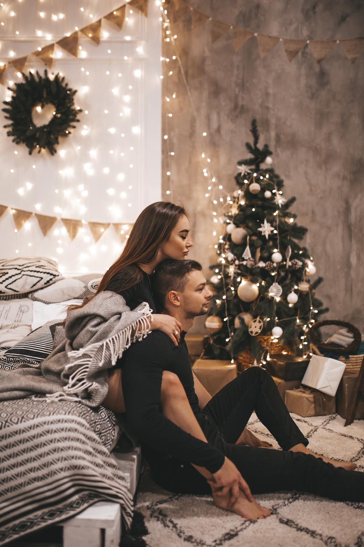 couple sitting beside Christmas tree