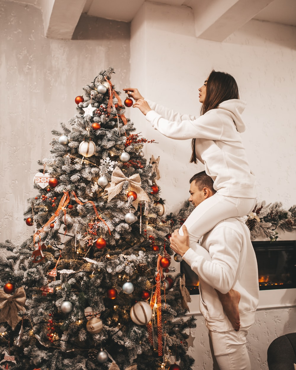 woman putting bauble on Christmas tree
