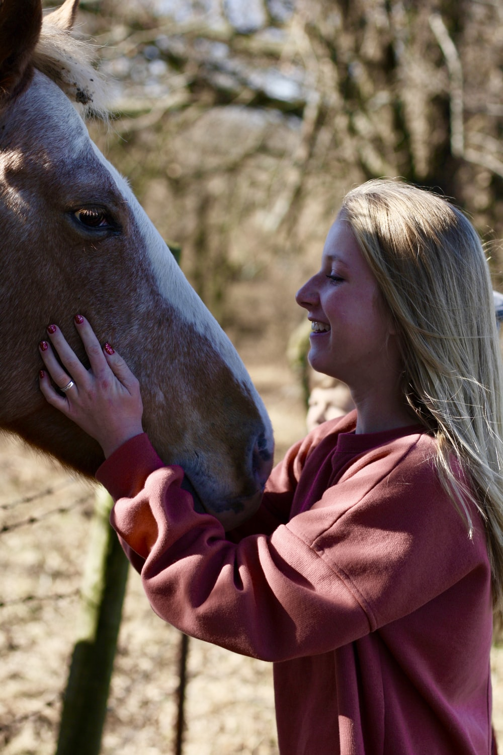 woman smiling and facing horse