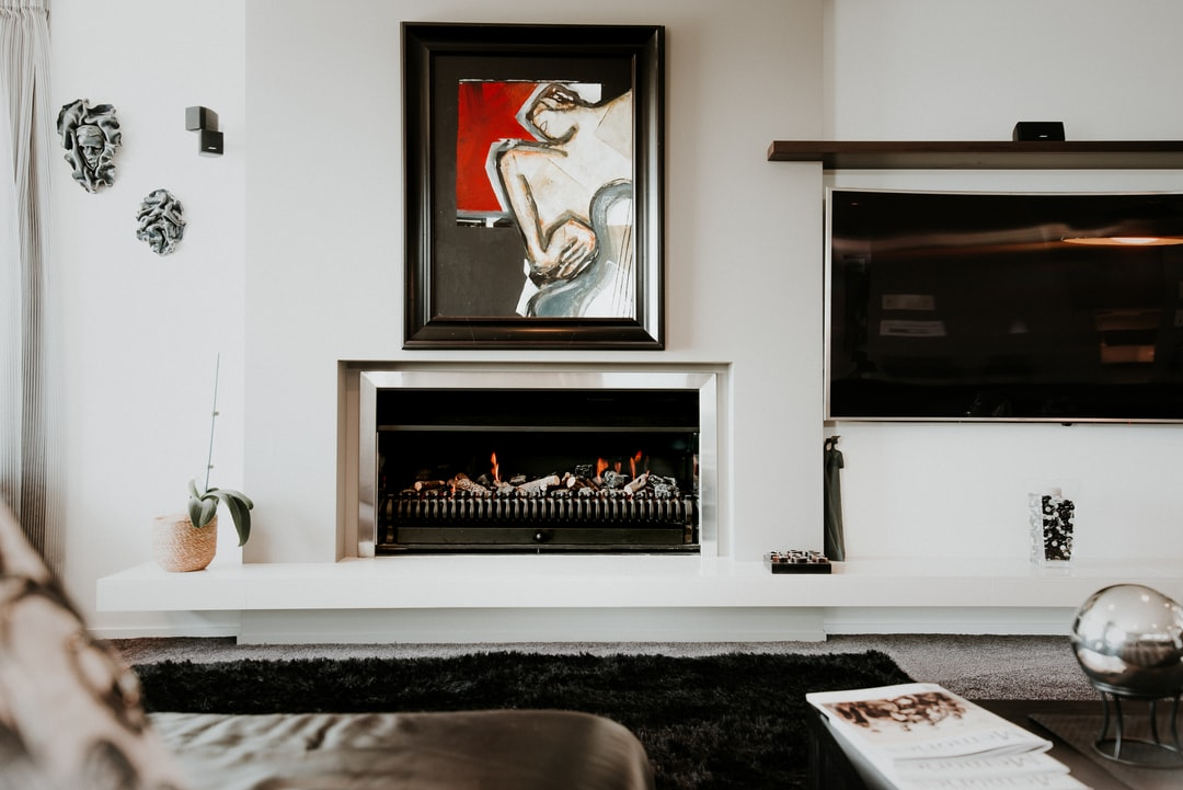 Black and White Modern Contemporary Living Room Interior From the View Of A Black Leather Sofa Looking On To A Black Rug, A Cozy  Lit Fireplace, A Silver, Curved Floor Lamp, And A Red & Black Art Picture In A Frame Featuring An Abstract Woman Or Lady.