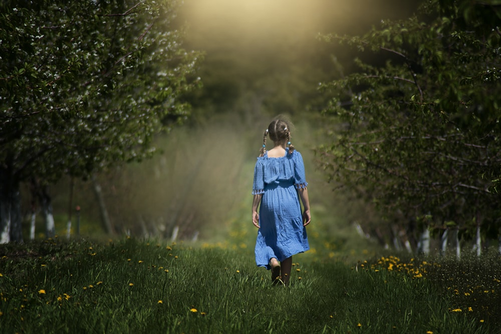 girl in blue dress walking on grass field by trees at daytime