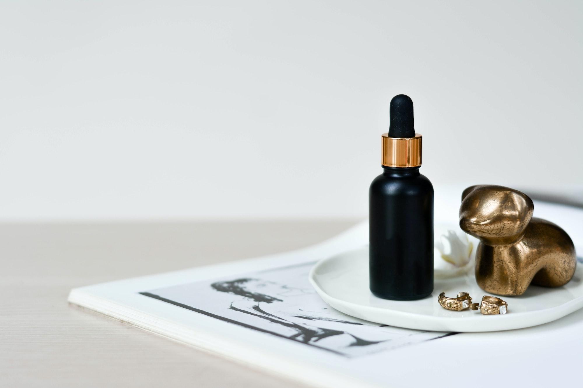 A black dropper bottle with gold details.