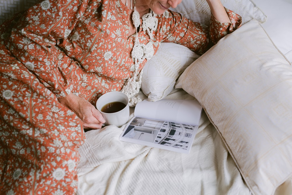 person in brown and white floral long-sleeved shirt lying in bed