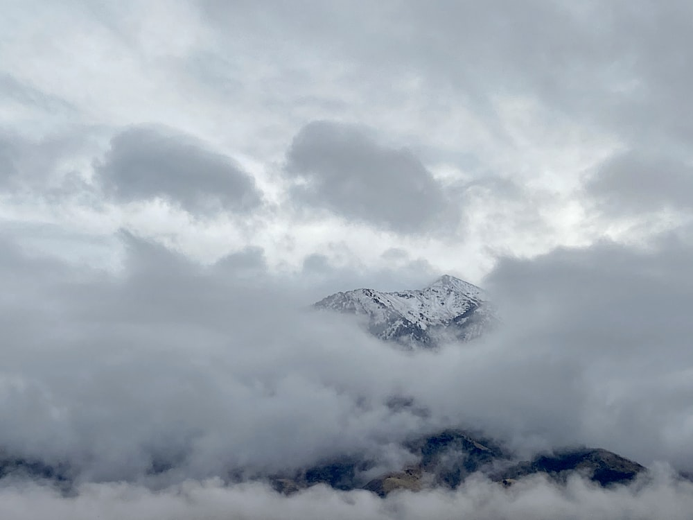 view photography of mountain covered by white clouds