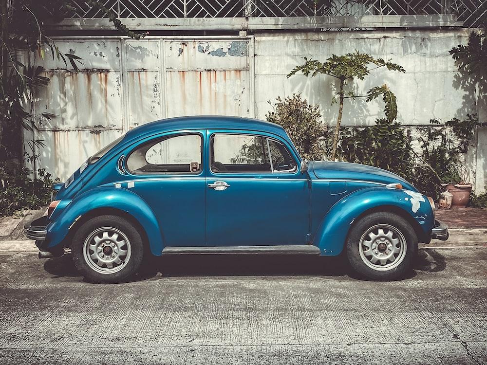 blue Volkswagen Beetle coupe parking near road