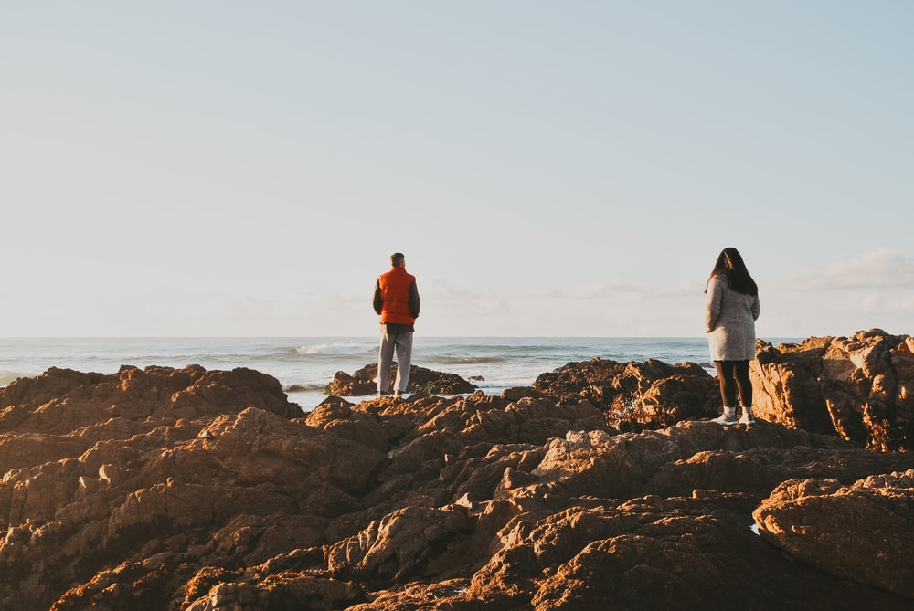 two person standing on brown rocks viewing body of water during daytime