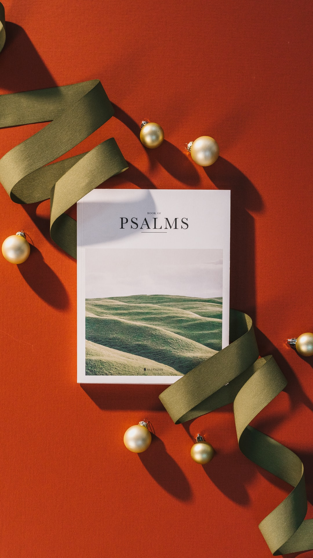 Book of Psalms with Christmas green ribbon and ornaments on a red background