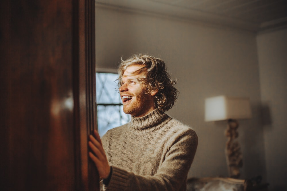 man wearing brown sweater standing and smiling near wall